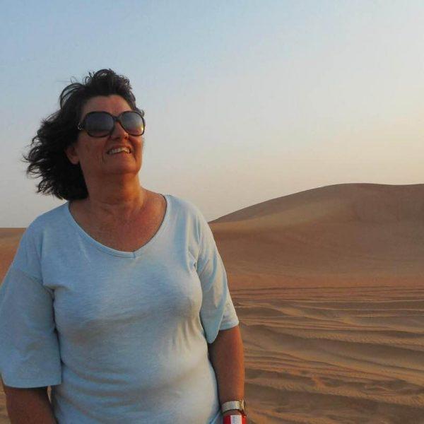 Carleeta smiling - it is dusk in the desert. Sandunes are behind her.